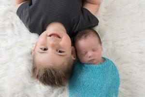 shooting photo naissance de bébé avec les aînés et grand frère lors d'une séance nouveau-né à collonges (01) près des Pays de Gex, Genève et de Haute savoie non loin de Genève en Suisse
